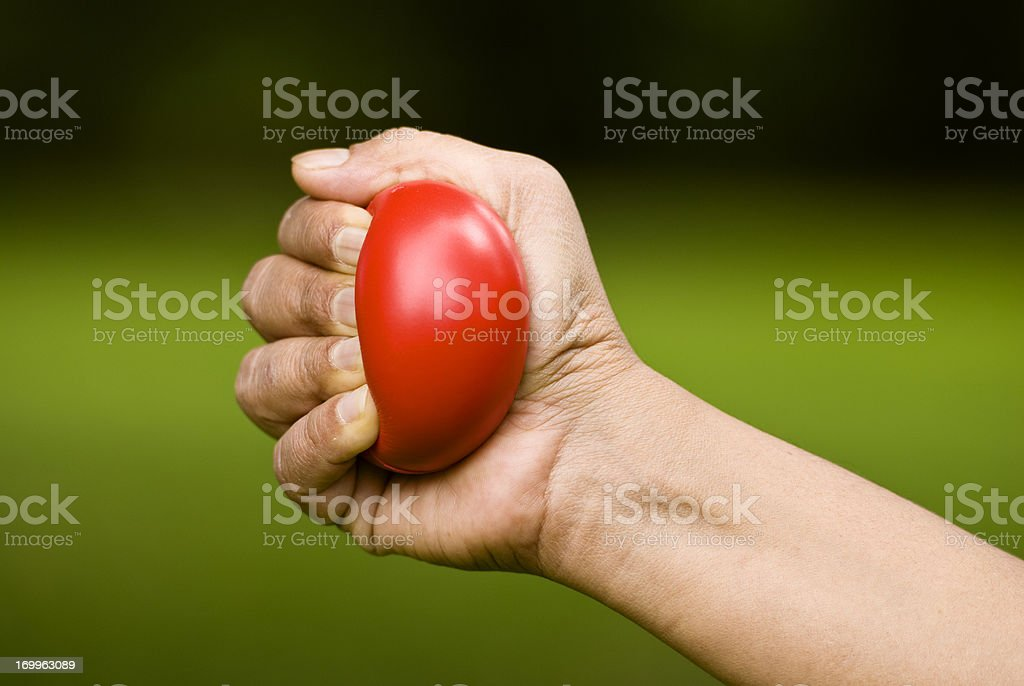 Hand squeezing a red stress ball stock photo