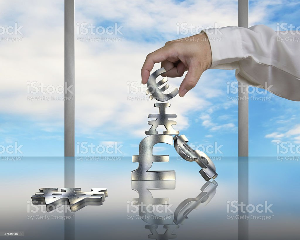 Hand stacking money symbols on table with reflection and sky stock photo