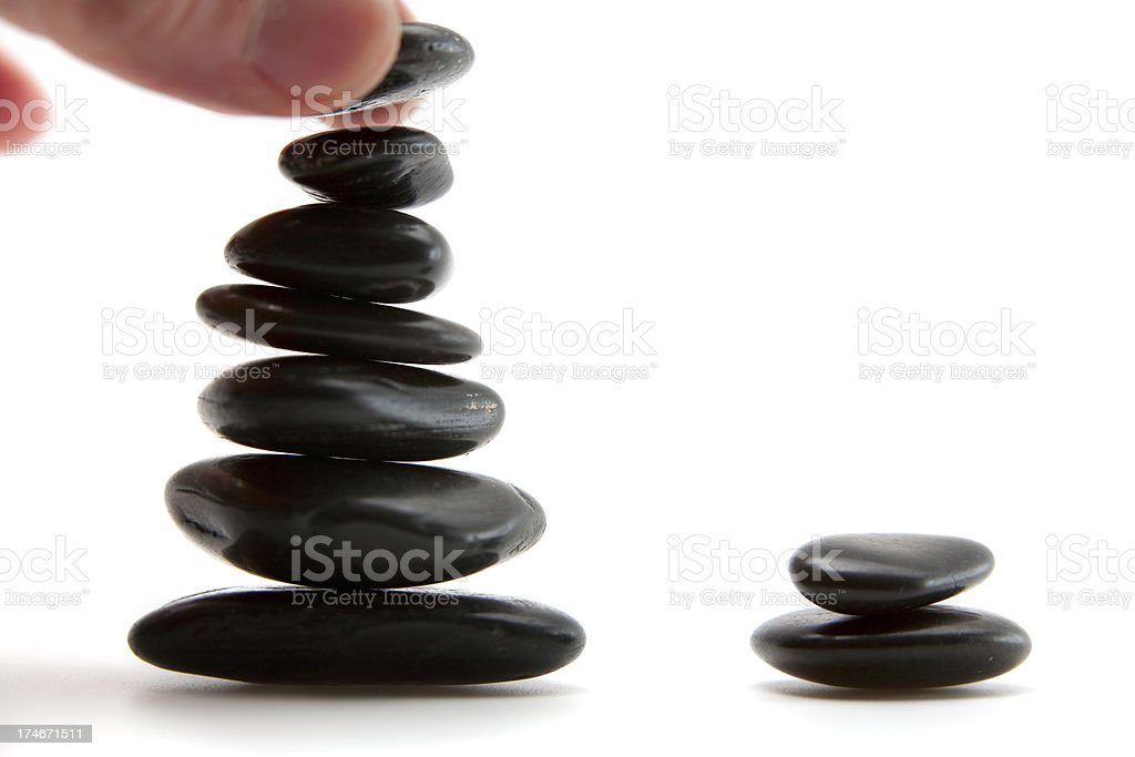 Hand stacking pebbles stock photo