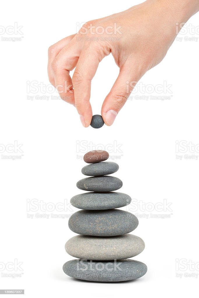 A hand stacking stones, large to small royalty-free stock photo