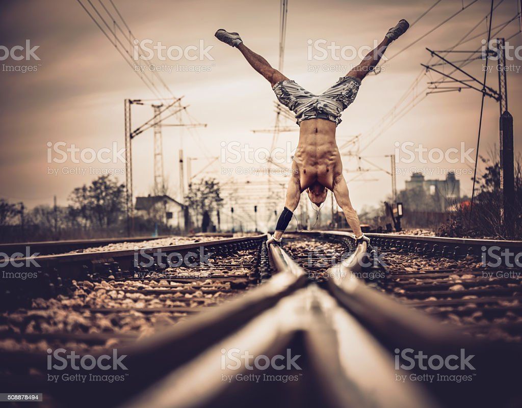 Hand stand on railroad tracks. stock photo