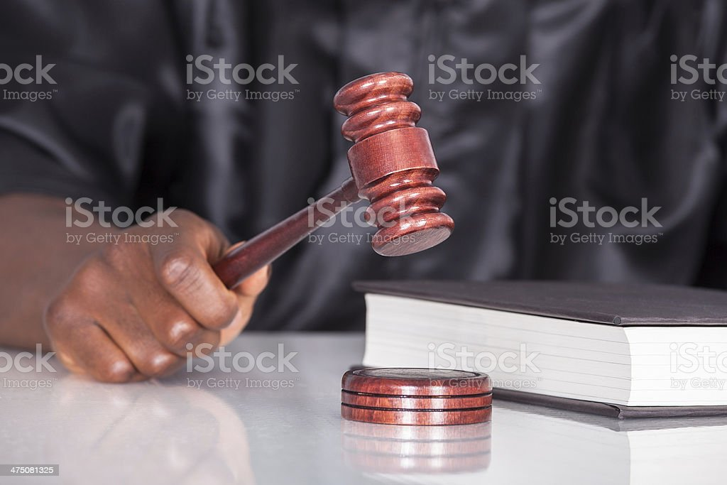 Hand Striking Gavel In A Courtroom stock photo