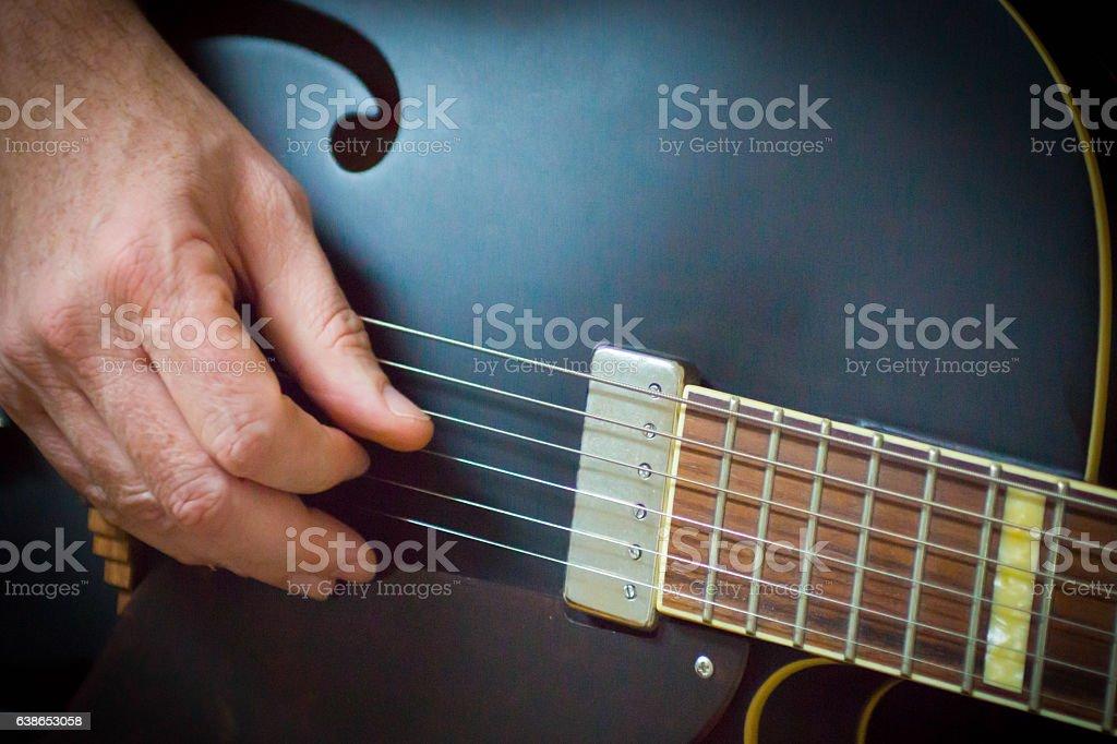 Hand strumming a guitar stock photo