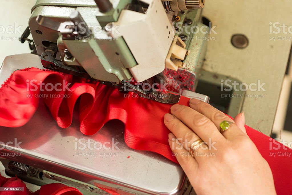 Hand Supporting Cloth Ruffled in Sewing Machine stock photo