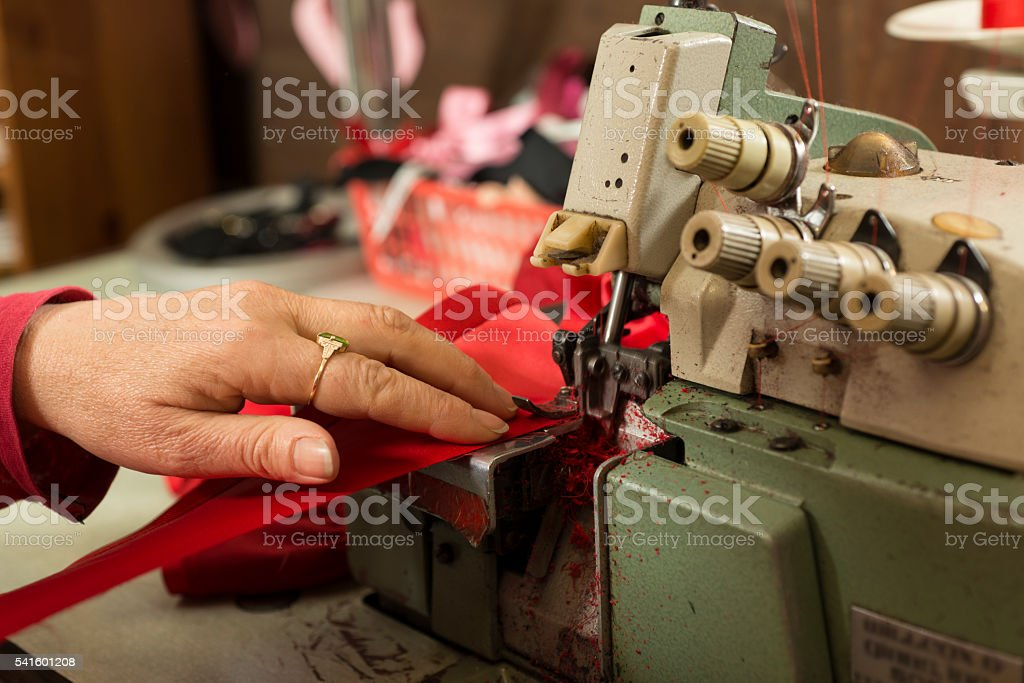 Hand Supporting Cloth Stitched in Sewing Machine stock photo