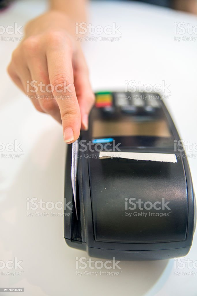 Hand swipe red credit through payment terminal. stock photo