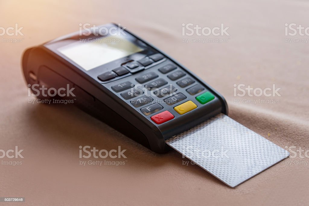 Hand Swiping Credit Card on POS terminal in Store stock photo