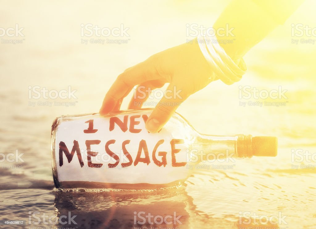Hand takes bottle saying '1 new message' from water's edge stock photo