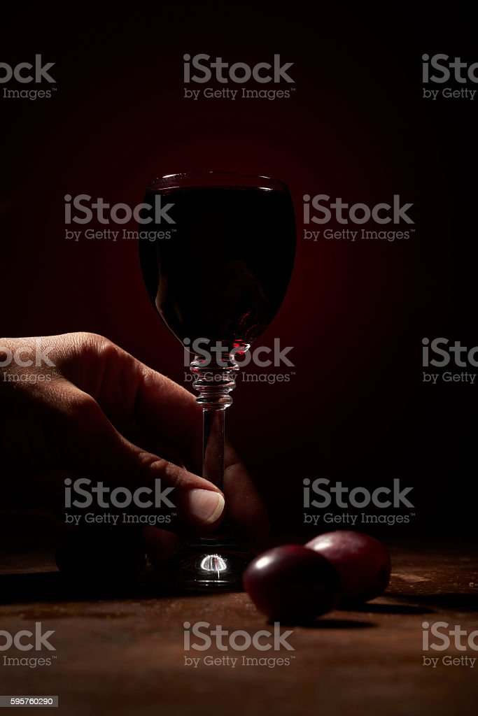 hand taking a glass of red wine stock photo