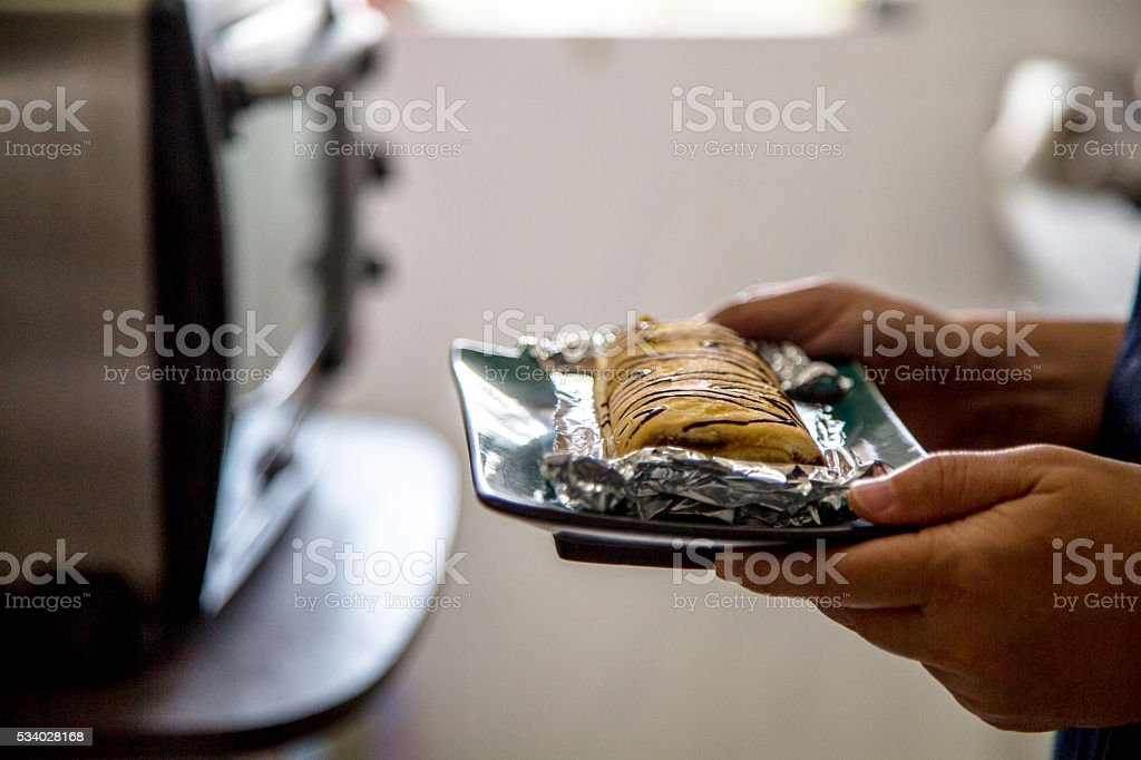 hand taking homemade cake from oven stock photo