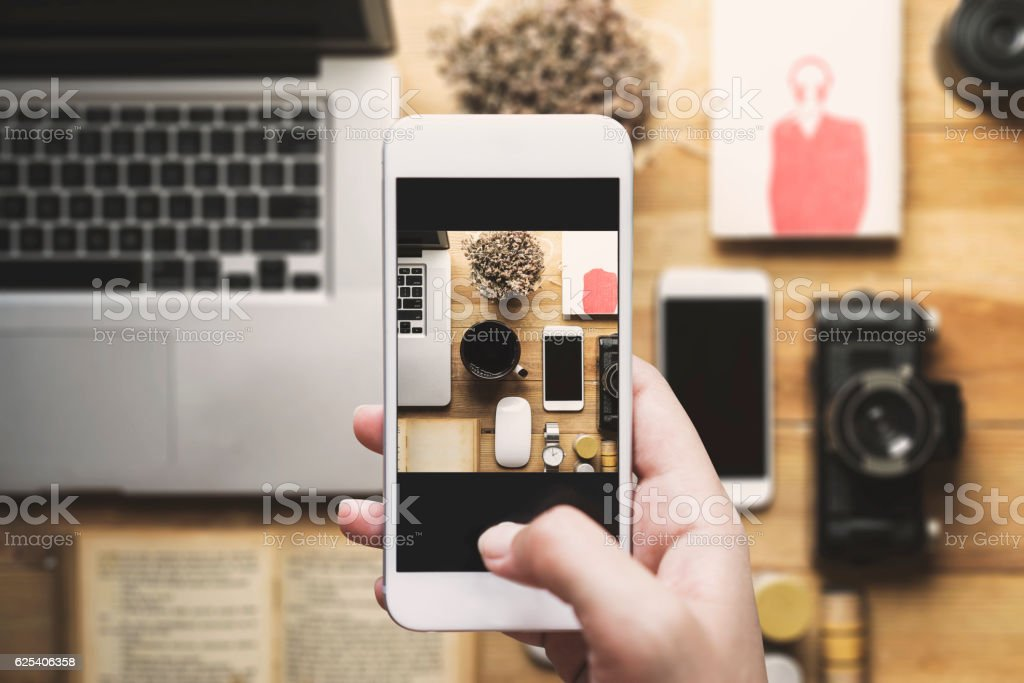 Hand taking photo with mobile phone, table top flat lay stock photo