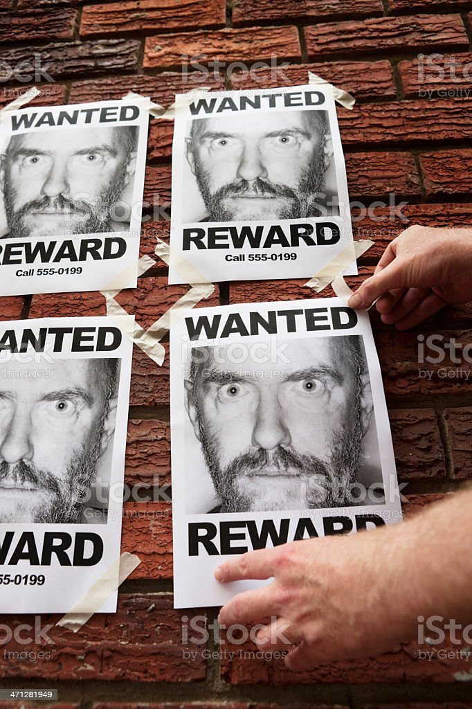 Hand tapes 'Wanted' posters of desperate looking man to wall stock photo