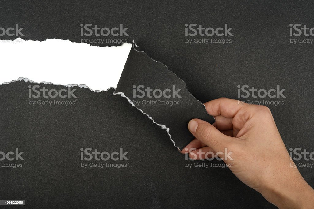 Hand Tear A Strip Of Black Paper stock photo