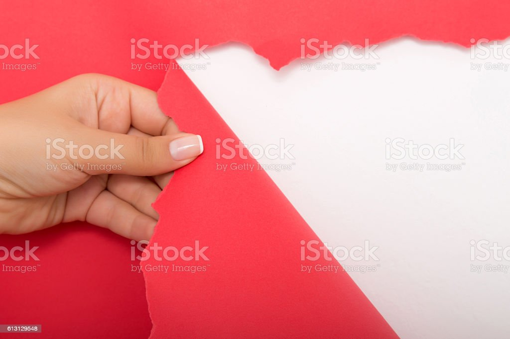 Hand tear a strip of red paper stock photo