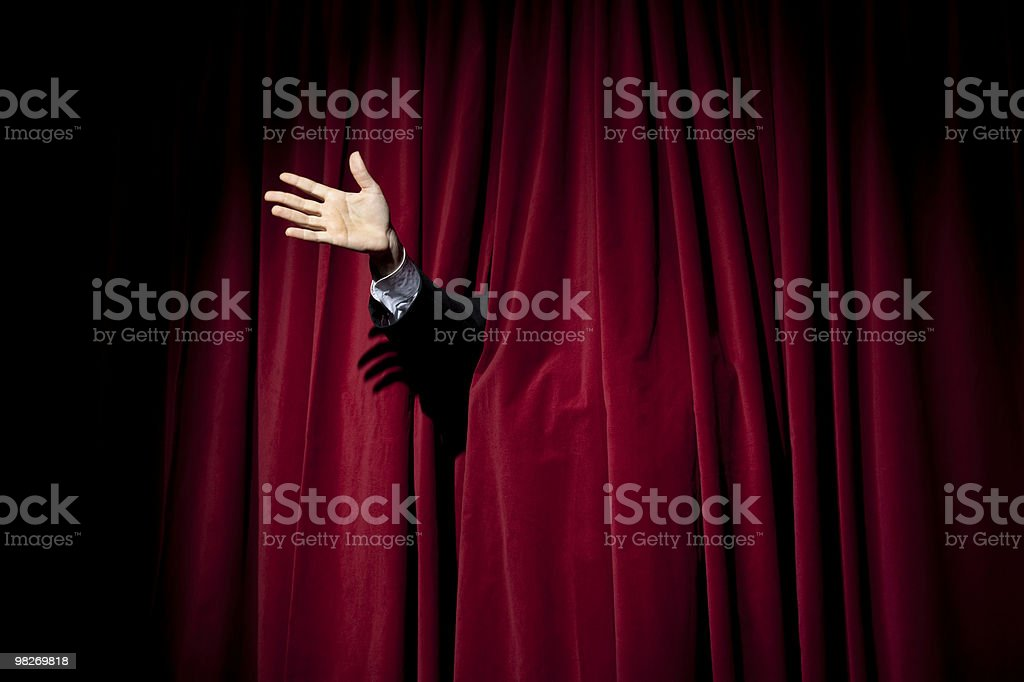 Hand through red curtain stock photo