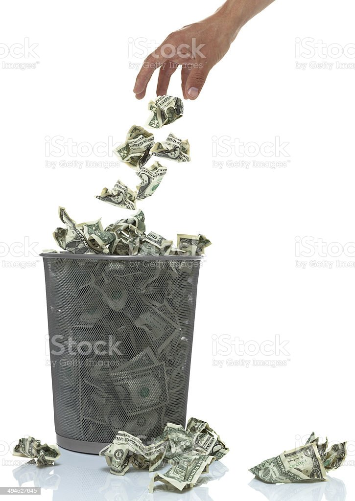 Hand throwing money into a trash can stock photo