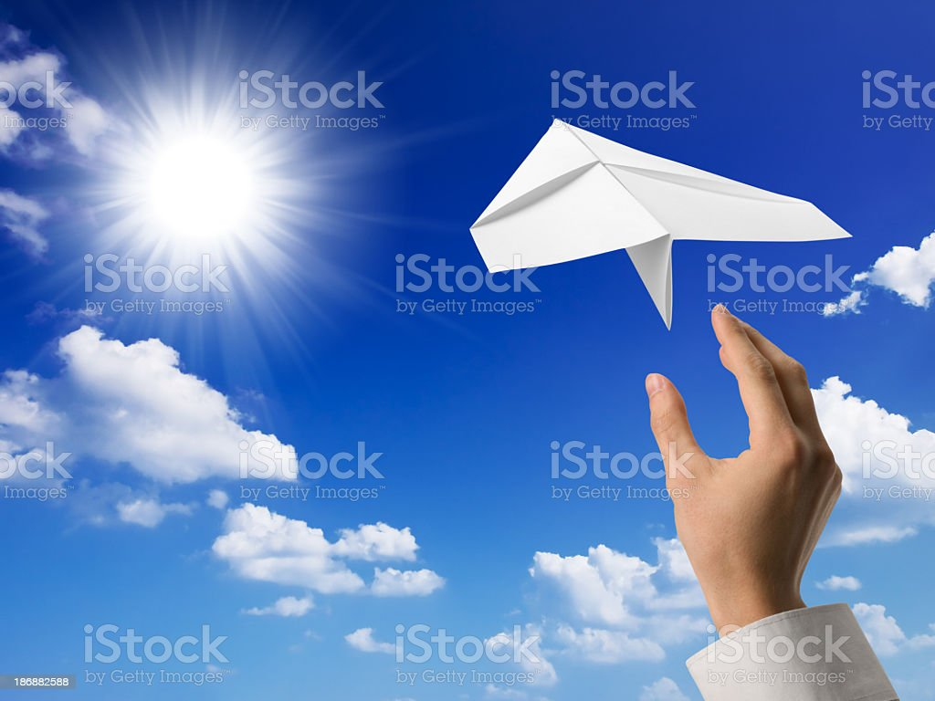 Hand throwing paper airplane into a blue sunny sky royalty-free stock photo