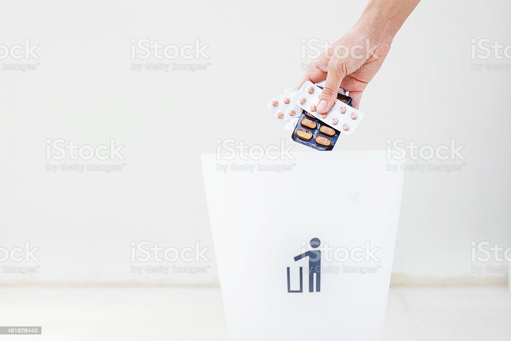 hand throwing pills in rubbish bin stock photo