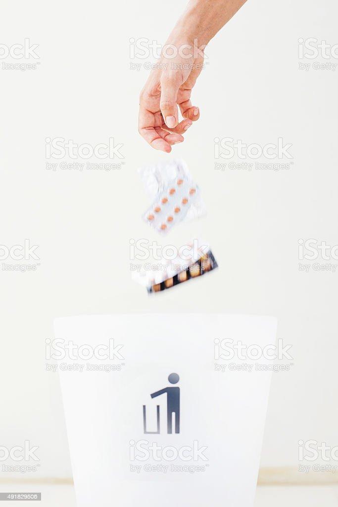hand throwing pills in rubbish bin stock photo