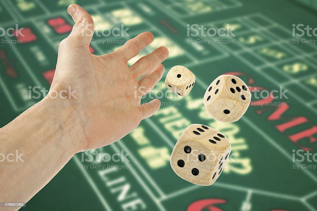 hand throwing three dices over casino table royalty-free stock photo