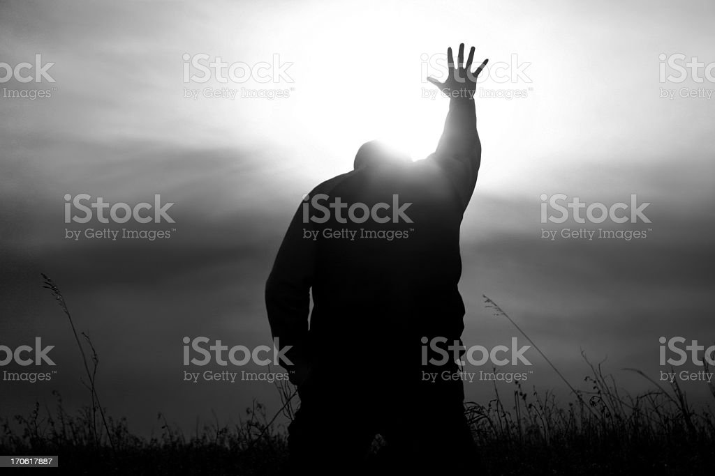 Hand to Heaven in Worship With God Rays stock photo