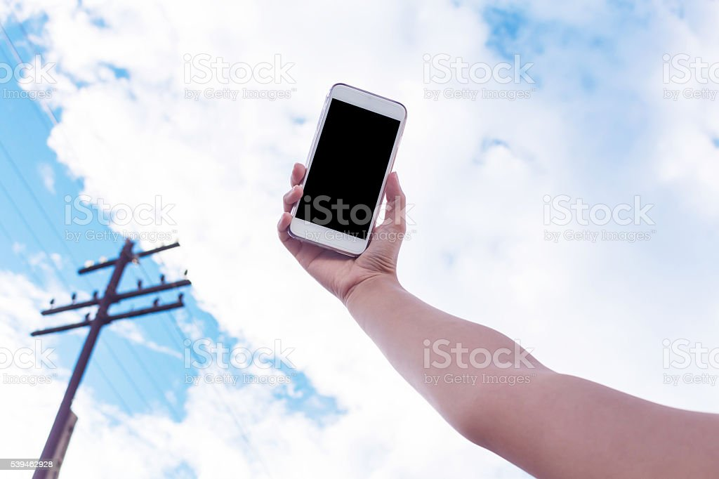 Hand to hold mobile phone on blue sky stock photo