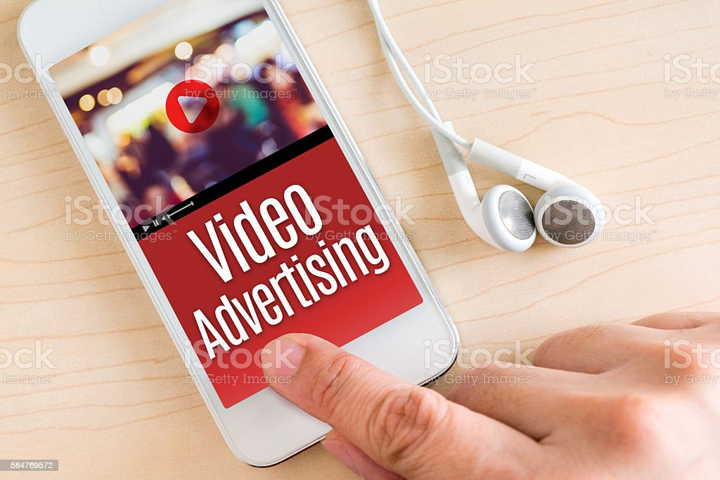 Hand touch smart phone and ear phone with Video Advertising stock photo