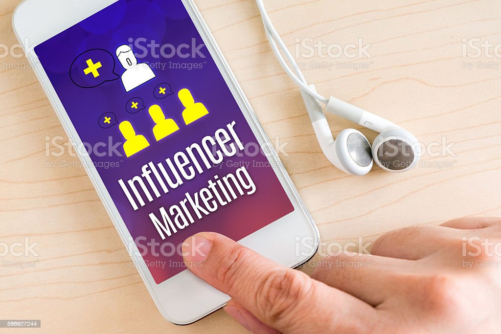 Hand touch smart phone with Influencer Marketing stock photo