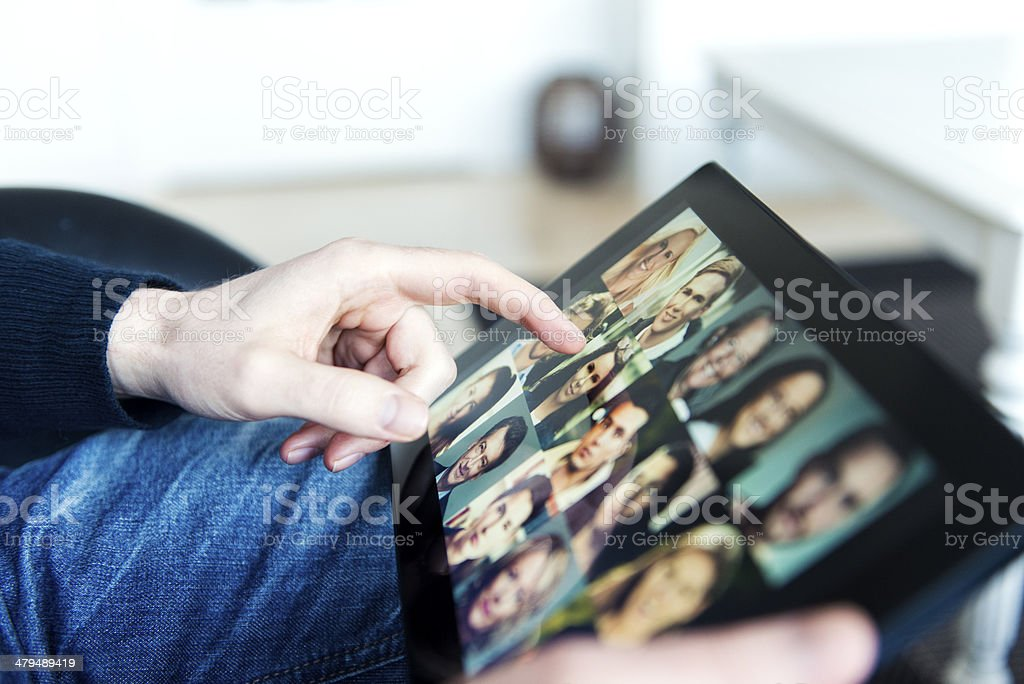 Hand touches digital tablet with profile pictures royalty-free stock photo