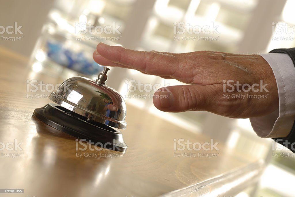 Hand touching a service bell on a countertop stock photo