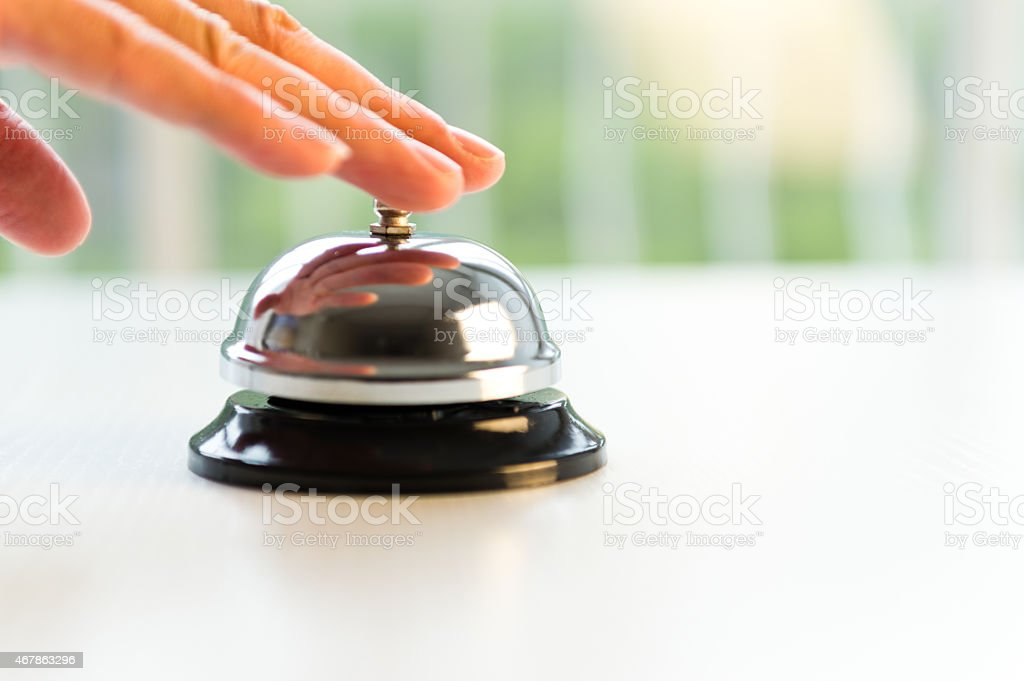 A hand touching hotel service bell stock photo