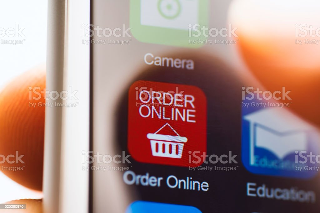 Hand touching online ordering app on phone screen stock photo
