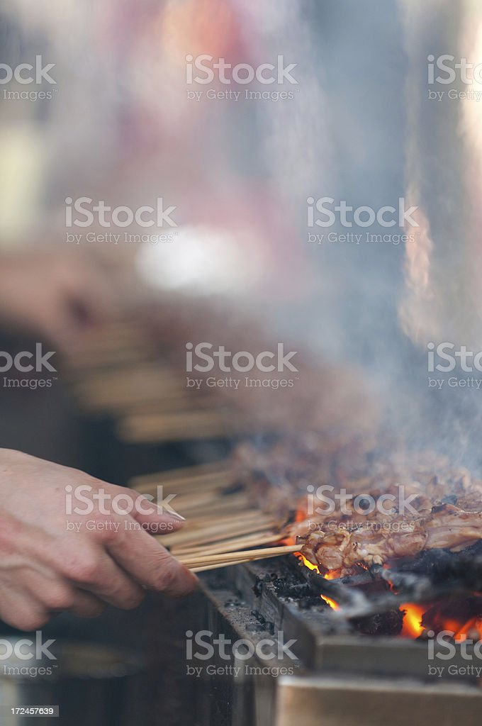 Hand Turning Barbequed Chicken Skewers on a Grill stock photo
