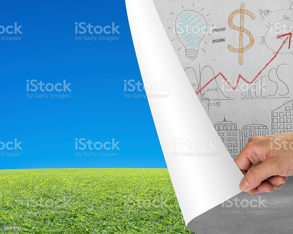 Hand turning business doodles chart page revealing nature sky me stock photo
