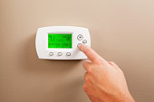 Hand Turning Down Digital Programmable Thermostat