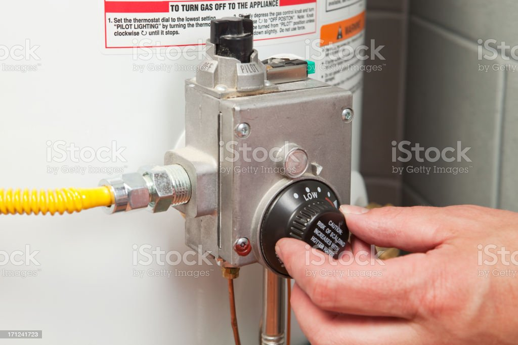 Hand Turning Down Water Heater Thermostat stock photo