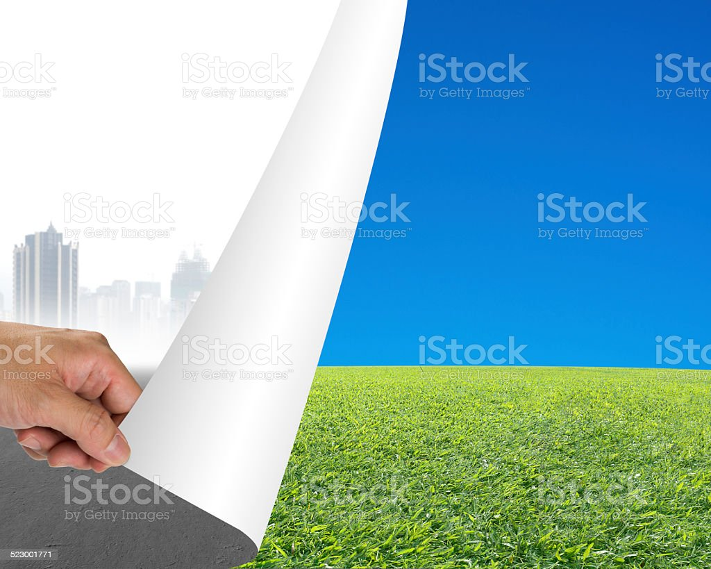 Hand turning gray cityscape page revealing nature sky meadow stock photo