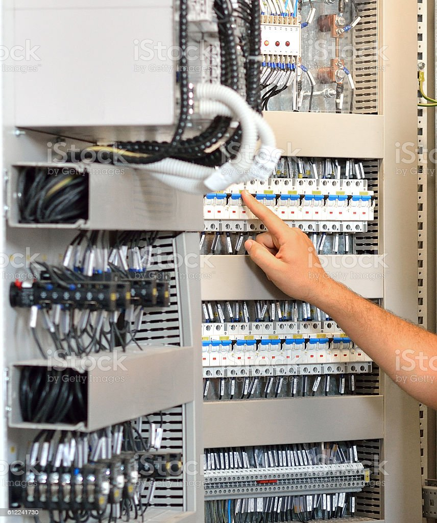 Hand Turning In or Off a Fuse Box Switch stock photo