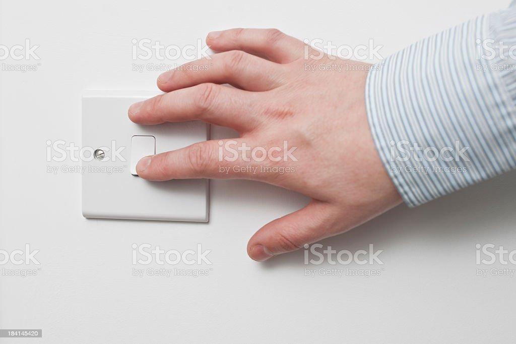 Hand turning light switch on. stock photo