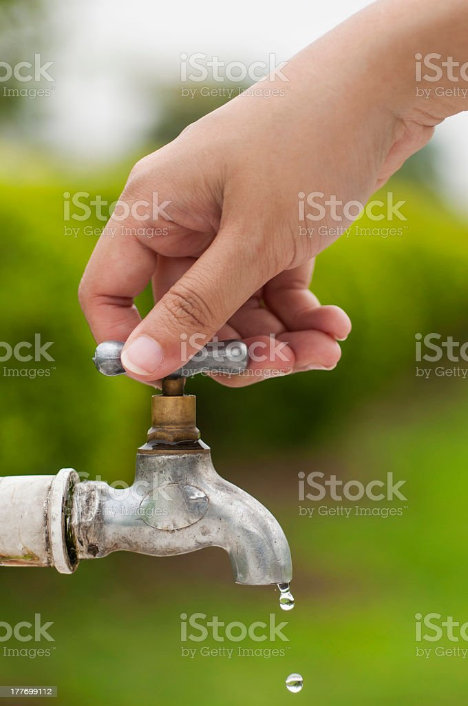 Hand turning off dripping outdoor water faucet stock photo