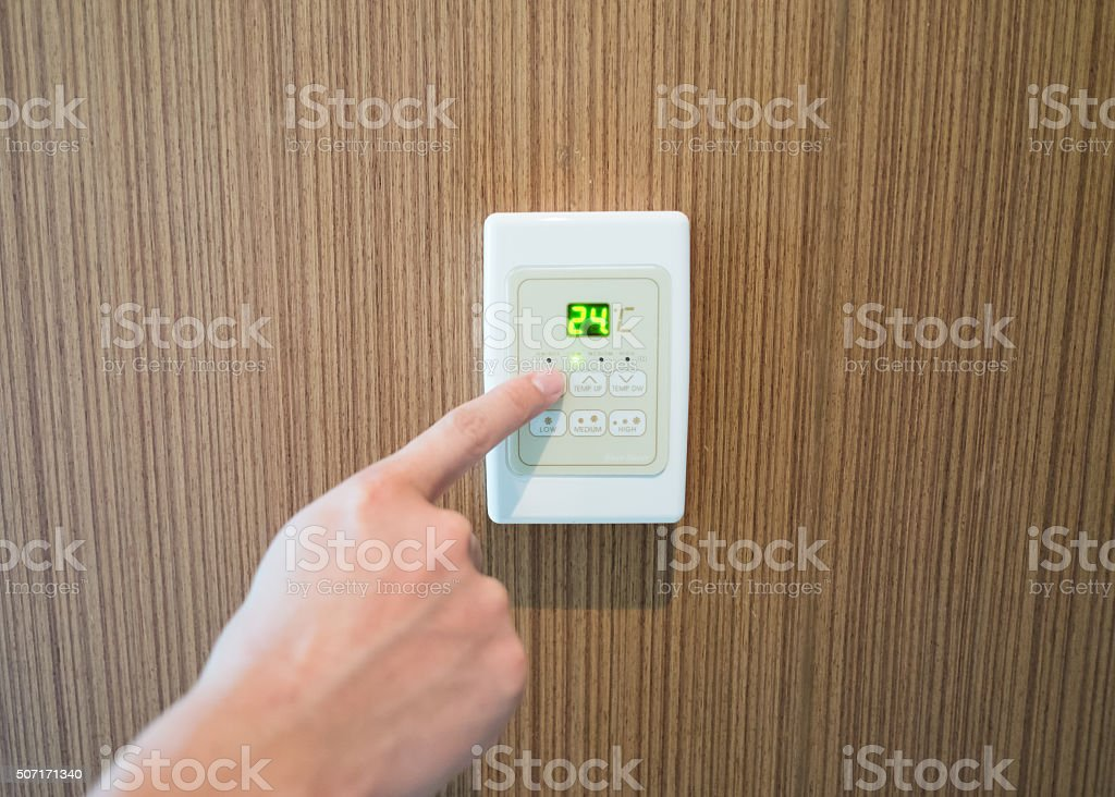 hand turning on and off air-condition panel mounted on wall stock photo