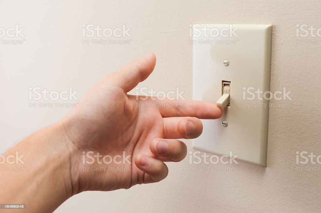 Hand turning wall light switch off stock photo
