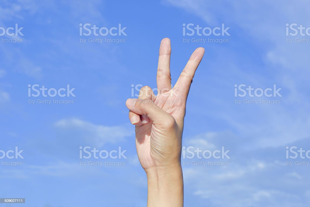 Hand two fingers up victory hand sign over blue sky royalty-free stock photo