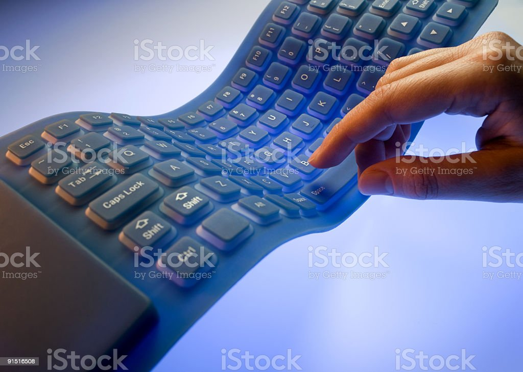 A hand typing on a flexible keyboard royalty-free stock photo