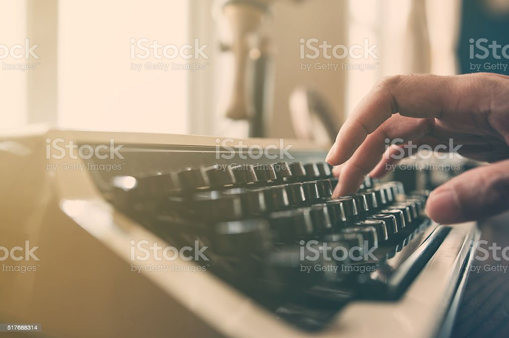 Hand typing on an vintage typewriter. stock photo