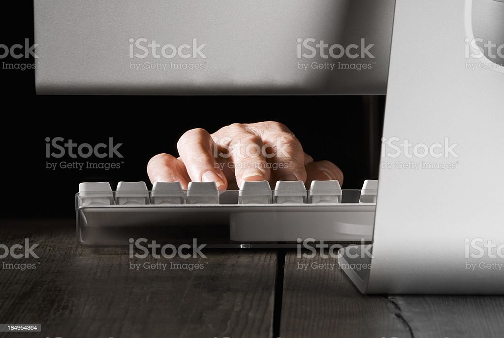 Hand typing on keyboard behind computer under torchlight stock photo