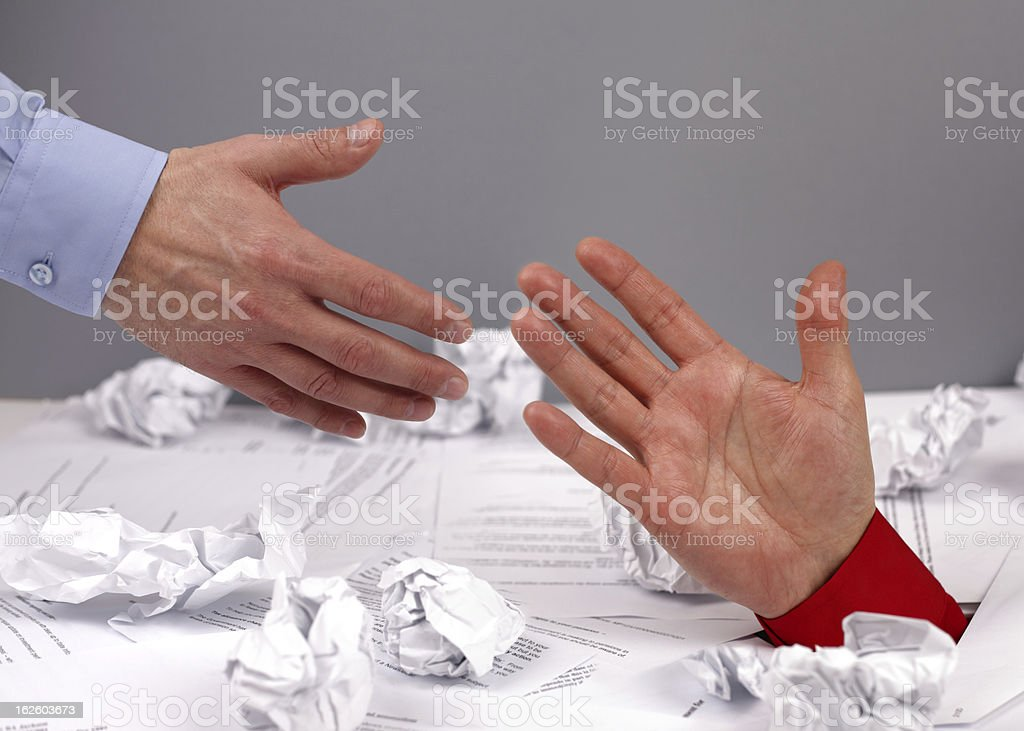 Hand under pile of paperwork reaching out to hand above stock photo
