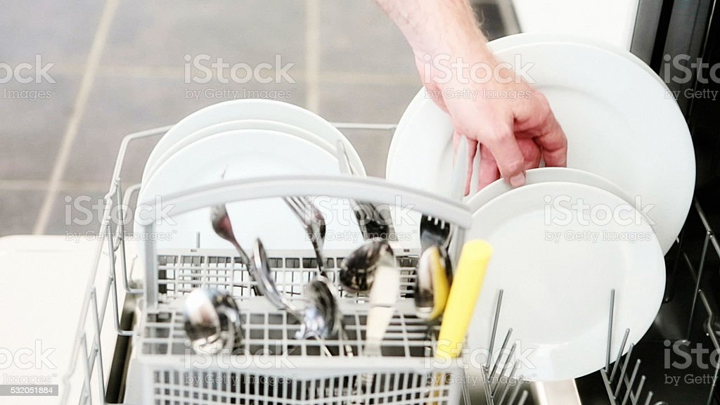 Hand unloading clean dishes from the dishwasher stock photo