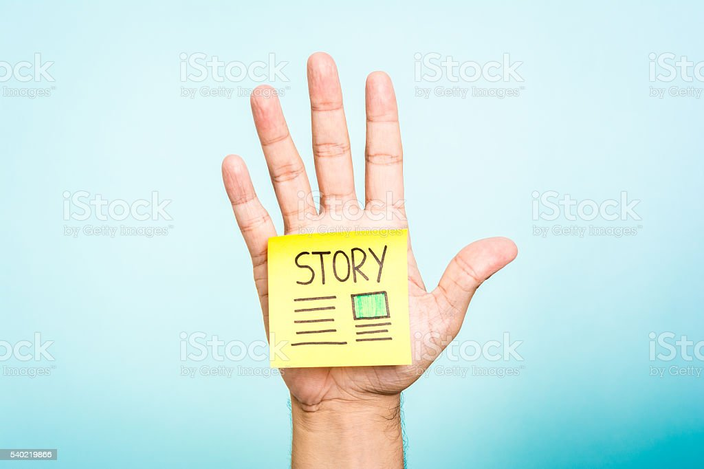 Hand up showing note with title 'Story' on blue background. stock photo