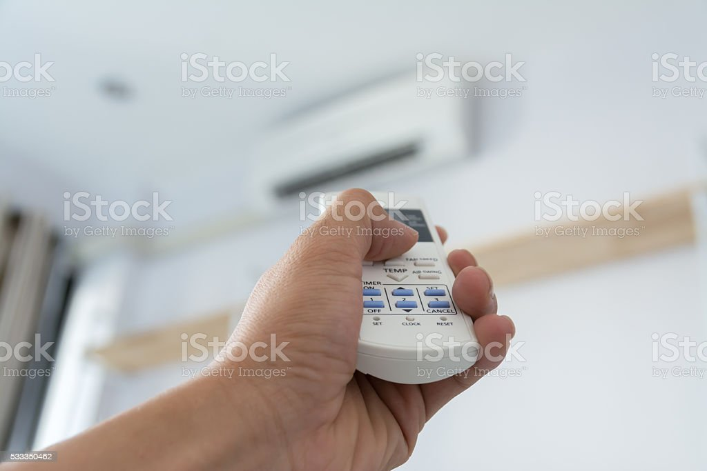 hand use remote control temp direct to air conditioner stock photo
